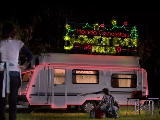 man and wife looking at caravan with neon sign 'Honda generators lowest ever prices'